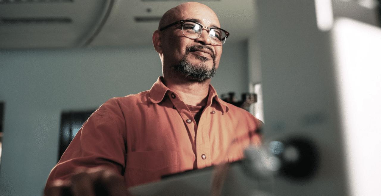 Man med glasögon kollar leende in i en datorskärm