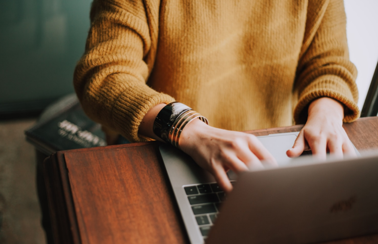 Kvinna med smycken och kofta skriver på datorn