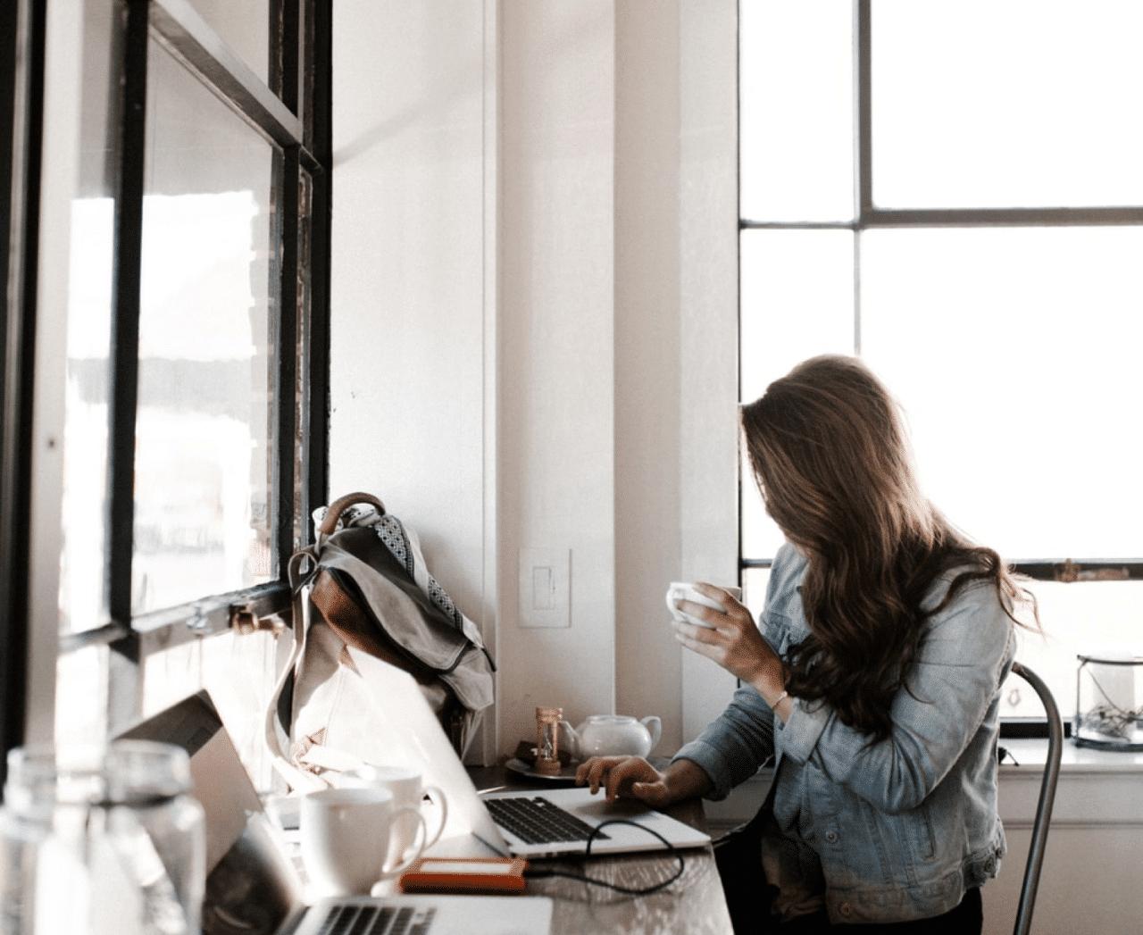 Kvinna skickar e post på ett kafé medans hon dricker kaffe