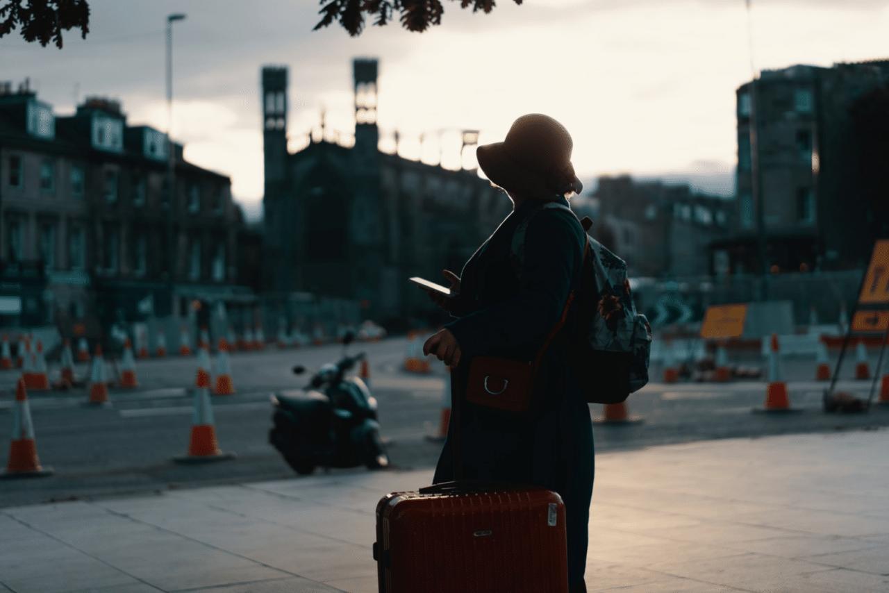 Turist står med resväskor och telefon i handen