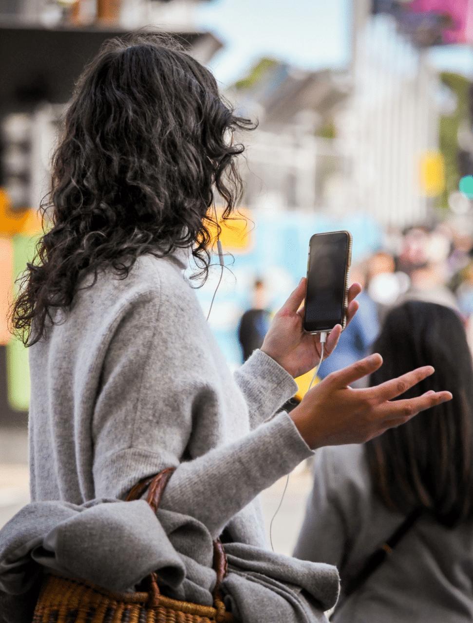 Kvinna använder videosamtal medans hon promenerar på gatan