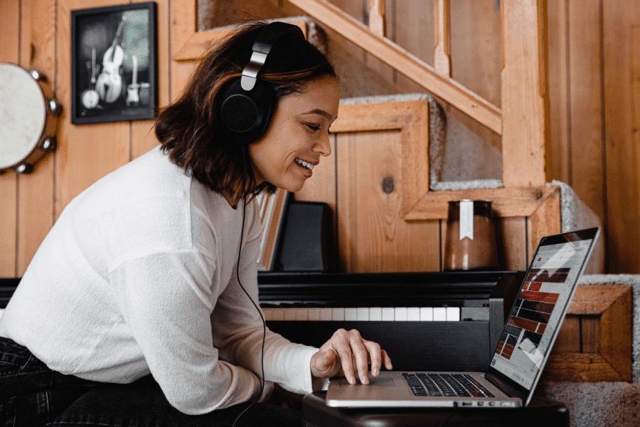 Leende kvinna med hörlurar använder laptop